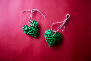 Decorative green hearts with threads on red background