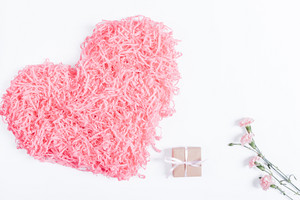 Decorative pink heart, small box with a gift and ribbon and flowers on a white background, top view