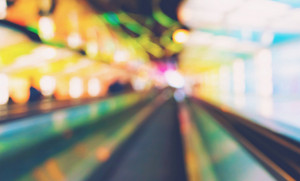 Defocused airport corridor with walking travelers