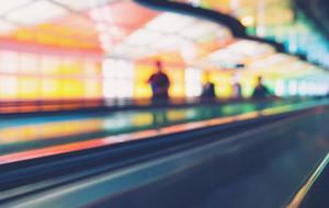 Defocused airport corridor with walking travelers