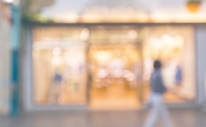 Defocused shopping mall interior store front with woman walking in pastel colors