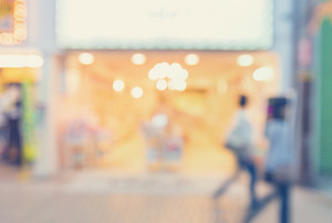 Defocused shopping mall interior store front with women walking in pastel colors