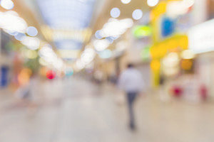 Defocused shopping mall interior with a man walking