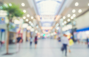 Defocused shopping mall interior with anonymous people walking