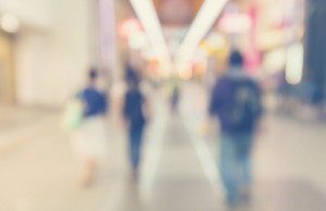 Defocused shopping mall interior with groups of people walking in pastel colors