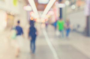 Defocused shopping mall interior with groups of people walking