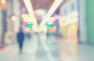 Defocused shopping mall interior with people walking in vintage style