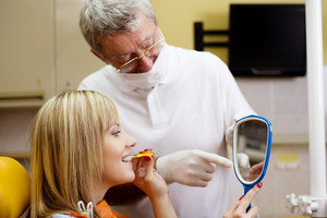 Dentist is showing the technique of teeth cleaning to his patient