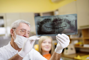 Dentist is showing the x ray of teeth to his patient