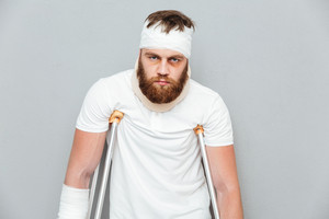Depressed tired young man standing with crutches over white background
