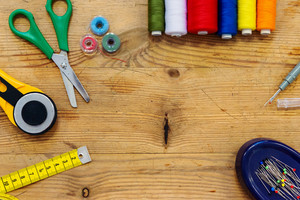 Desk of a tailor with scissors, colorful threads, pins, tape measure an other objects, flat lay, copy space