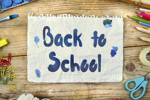 Desk of an artist with Back to school sign. Studio shot on wooden background.