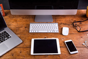 Desk with gadgets and office stuff. Computer keyboard, notebook, smart phone and tablet around the workplace. Flat lay. Studio shot on wooden background.