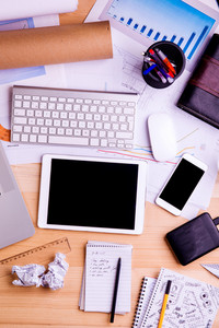 Desk with gadgets, office supplies and chart graph. Computer keyboard, tablet, smart phone and stationery around the workplace. Flat lay. Studio shot on wooden background.