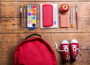 Desk with school supplies. Studio shot on wooden background.