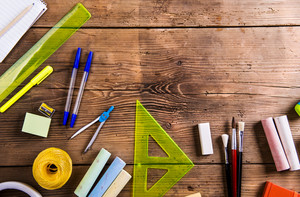 Desk with stationary and with Back to school sign. Studio shot on wooden background.