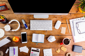 Desk with various gadgets and office supplies. Computer, smart phone and other devices and stationery around the workplace. Flat lay.