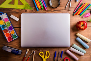 Desk with various school supplies and closed notebook  in the middle . Studio shot on wooden background, frame composition, empty copy space