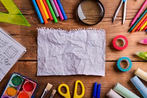 Desk with various school supplies and crumpled empty squared paper  in the middle . Studio shot on wooden background, frame composition, empty copy space