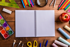 Desk with various school supplies and empty lined paper notebook  in the middle . Studio shot on wooden background, frame composition, empty copy space