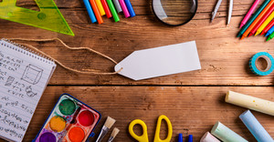 Desk with various school supplies and empty paper tag in the middle . Studio shot on wooden background, frame composition, empty copy space