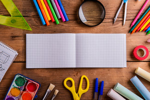 Desk with various school supplies and empty squared paper notebook  in the middle . Studio shot on wooden background, frame composition, empty copy space