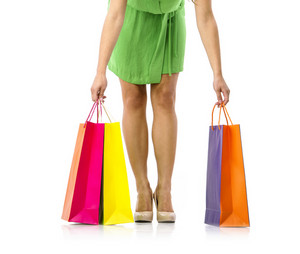 Detail of a beautiful young woman's legs with shopping bags, isolated on white background