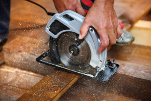 Detail of carpenters hand grinding wooden planks