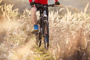 Detail of cyclist man riding mountain bike on outdoor trail in nature