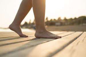 Detail of female barefoot feet on sunny beach