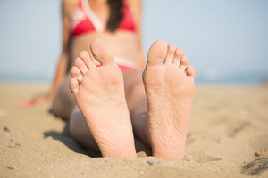 Detail of female barefoot feet on sunny beach
