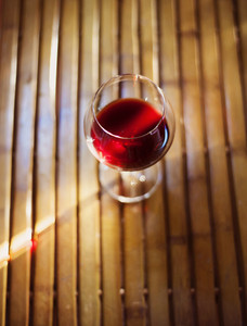 Detail of glass of red wine on woodden floor
