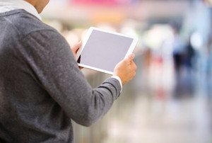 Detail of man hands holding tablet in shopping centre
