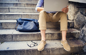 Detail of modern hipster man´s feet sitting on the stairs and using laptop