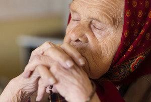 Detail of very old woman in head scarf praying