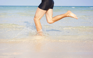 Detail of young man running at paradise beach in Phu quoc island, south of vietnam