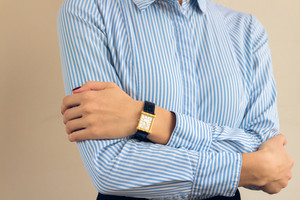 Details of clothing. A woman in a blue shirt with stripes, on her hand a gold watch.