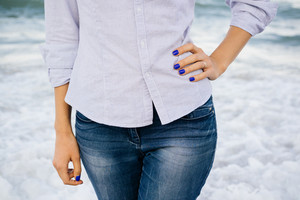 Details of clothing. The woman in jeans and shirt standing in the sea foam on the beach. In her hands blue manicure.
