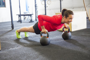 Determined Woman Doing Pushups On Kettlebell In Health Club