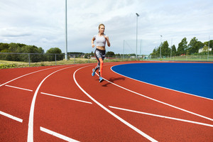 Determined Woman Running On Sports Tracks
