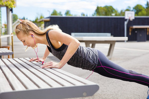Determined Young Woman Doing Pushups On Bench
