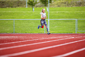 Determined Young Woman Running On Sports Tracks