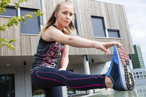 Determined Young Woman Stretching Her Leg Against Building