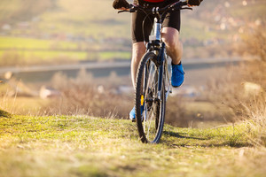 Detial of cyclist man legs riding mountain bike on outdoor trail in nature