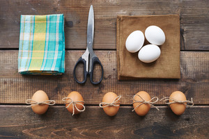 Different eggs, scissors, linen and cotton napkins on wooden background