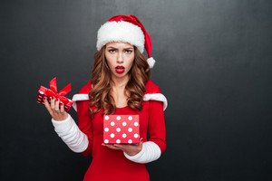 Disappointed young woman in xmas outfit standing with open present box over black background