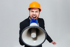 Displeased bearded engineer shouting in megaphone and looking at camera. Isolated gray background