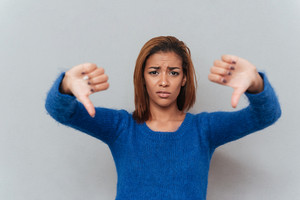 Displeased young african woman in sweater showing thumbs down. Isolated gray background