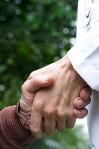 Doctor helping senior lady, holding her hand