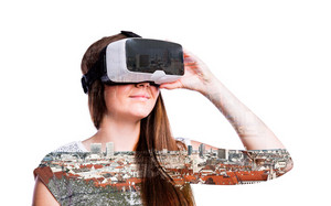 Double exposure. Beautiful woman wearing virtual reality goggles, smiling. Roofs of various buildings.